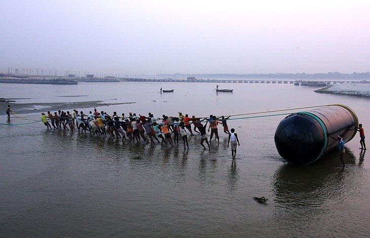 Рабочие тянут понтон к реке Ганг во время подготовки к «Празднику кувшинов»
