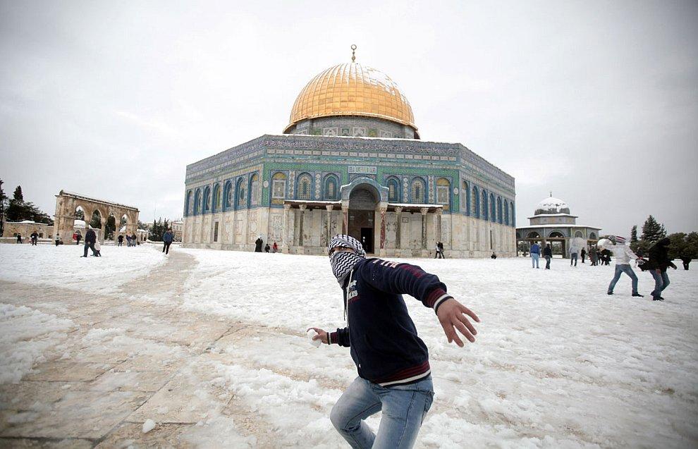 Палестинец кидает снежки по израильтянам около мечети аль-Акса на Храмовой горе Иерусалима