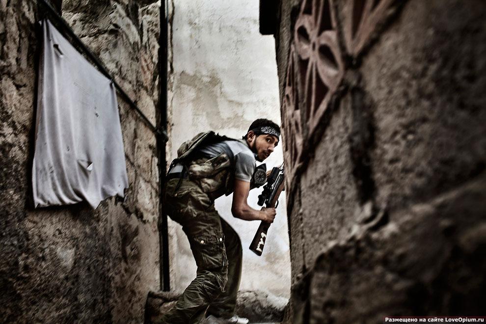 Сирийский мятежник занимает огневую позицию по время столкновений с правительственными войсками в городе Алеппо
