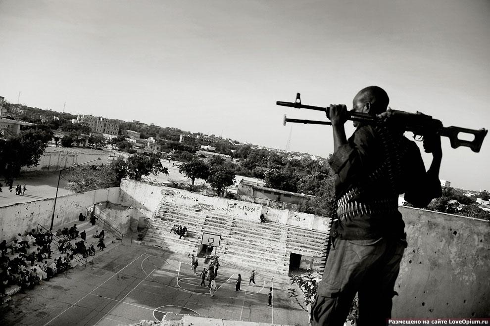 Вооруженный охранник следит за порядком во время женского баскетбольного матча в Могадишо, Сомали