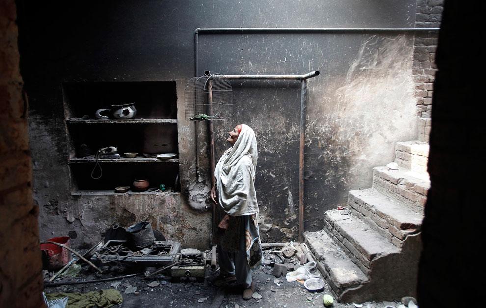 Женщина смотрит на свою погибшую птицу в собственном доме, Лахор