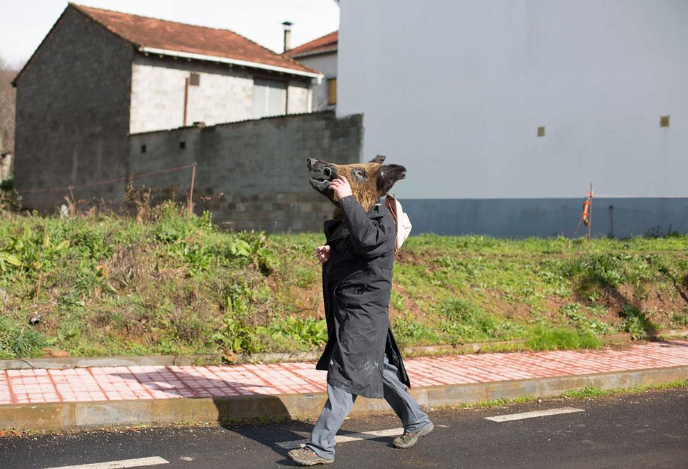 Человек идет с головой кабана во время фестиваля «O Entroido» в деревне Лаза, Испания