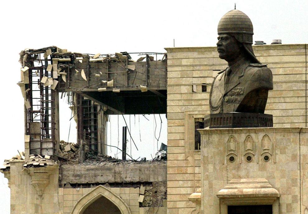 Статуя президента Ирака Саддама Хусейна и его дворец, пострадавший во время авиаударов коалиции