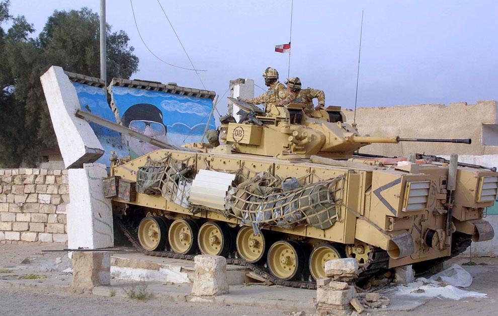 Британская бронемашина сносит изображение Саддама Хуссейна в городе Басра на юге Ирака