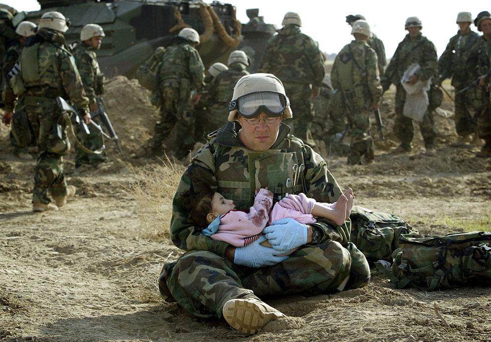 Американский военный с иракским ребенком, которого потеряли родители во время обстрела территории