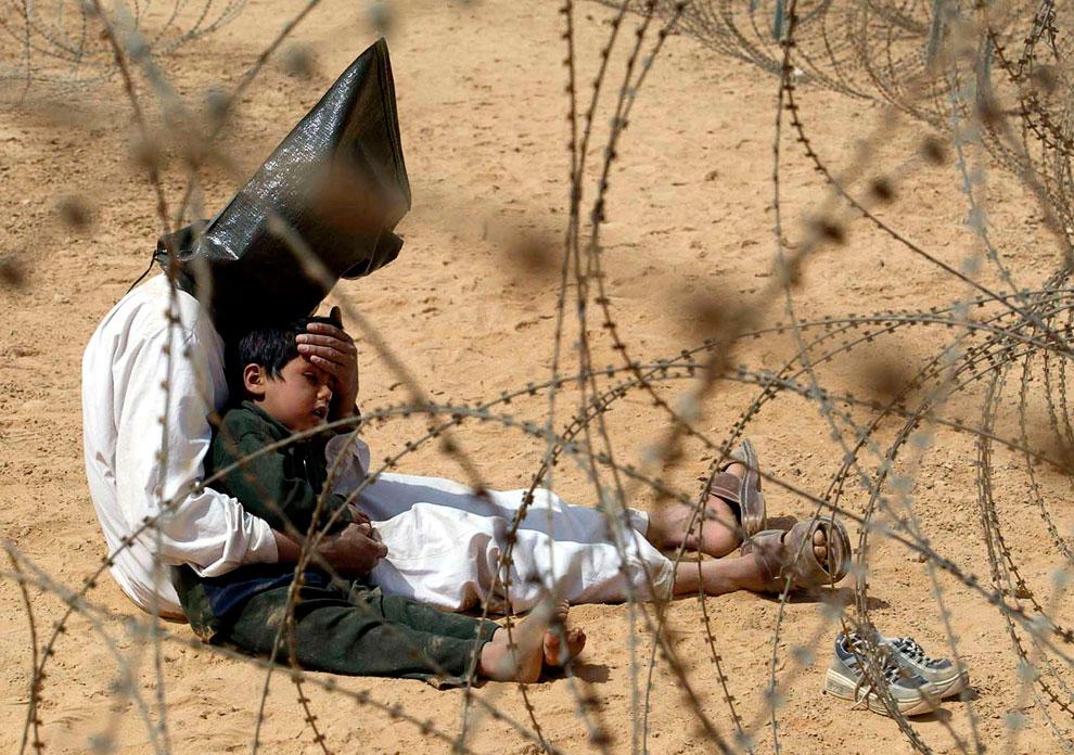 Иракский мужчина с мешком на голове, захваченный в плен со своим сыном