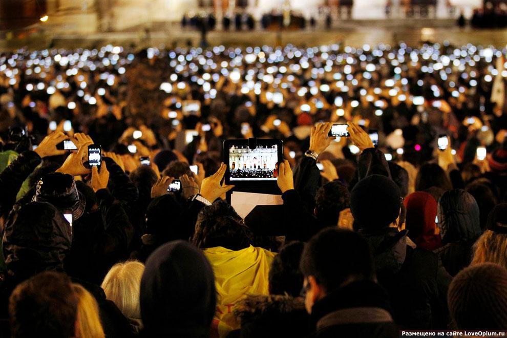 Люди на площади перед собором Святого Петра пытаются сфотографировать нового Папу Римского