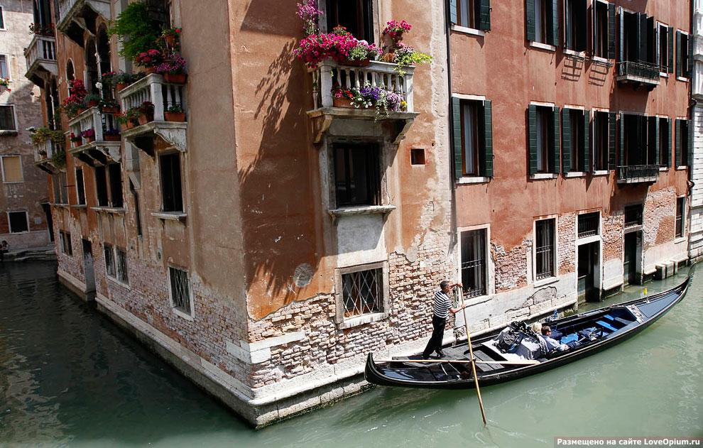 Гондольер катает туристов по каналам Венеции
