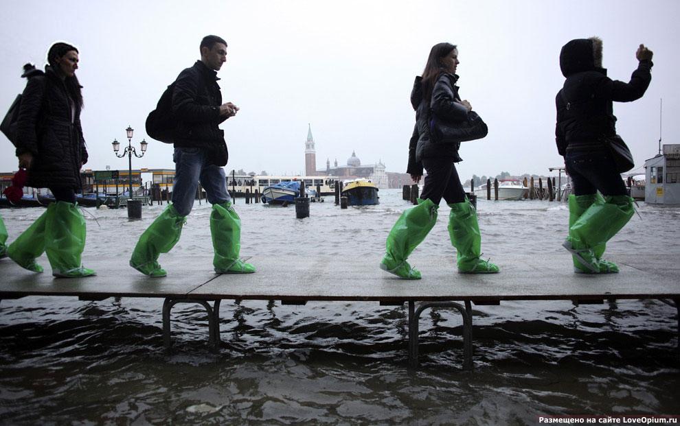Время от времени Венецию затапливает и тогда туристам приходится ходить по городу в специальной одежде по специальным временным мостикам