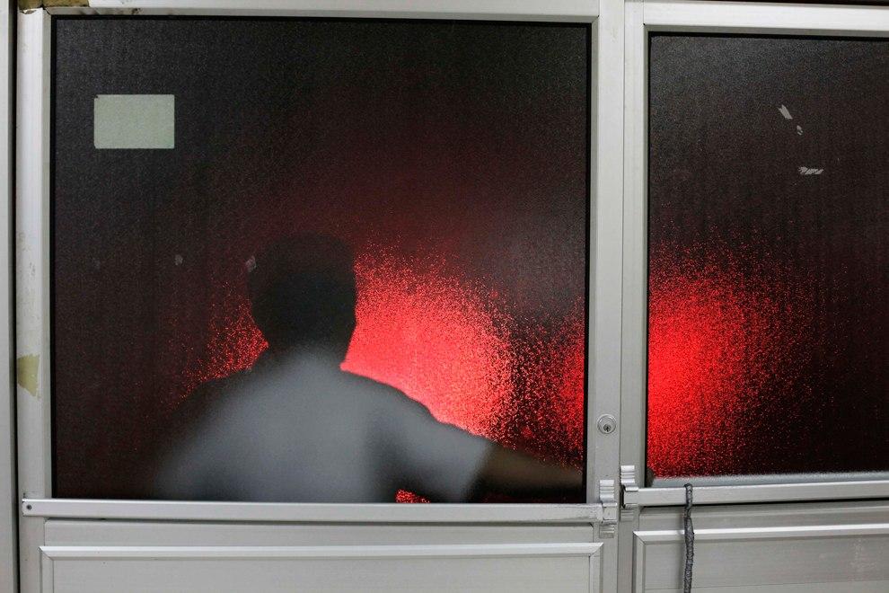 Охранник дежурит у двери отделения неотложной помощи в больнице в Сан-Педро-Сула