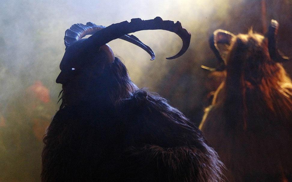 Человек в маске демона, которая сделана из кедрового дерева с козьими рогами