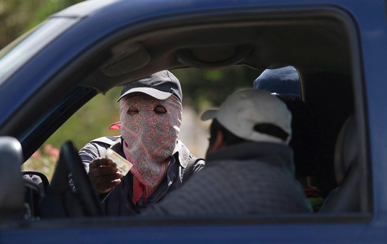 Вооруженный человек в маске проверяет личность водителя на контрольно-пропускном пункте на въезде в город Эль-Перикон, Мексика