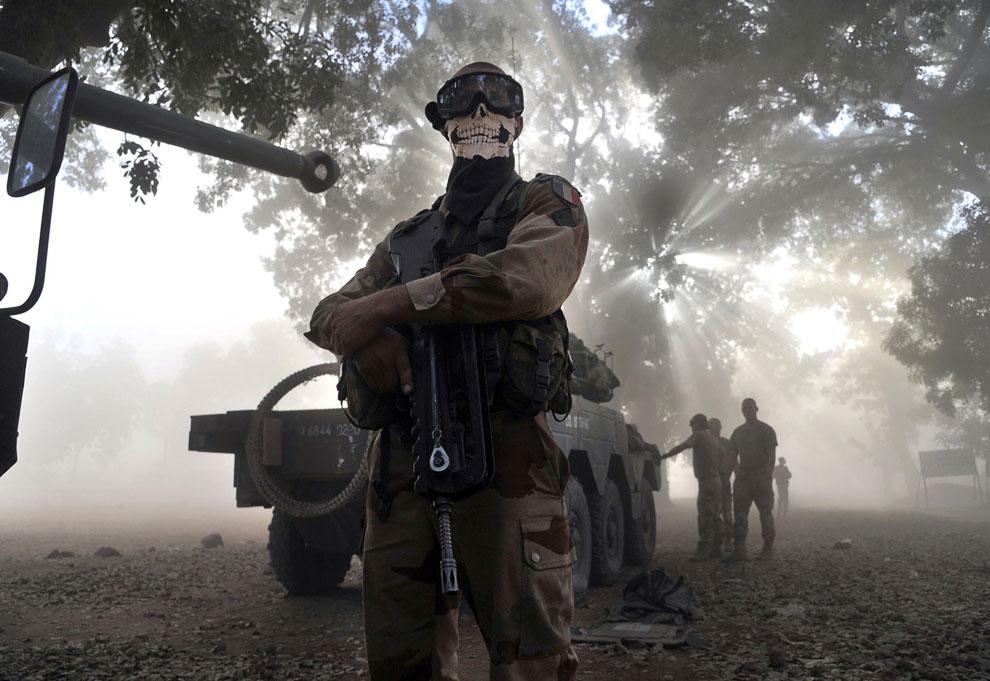Экстравагантный французский солдат рядом с бронемашиной на улице в Нионо, Мали