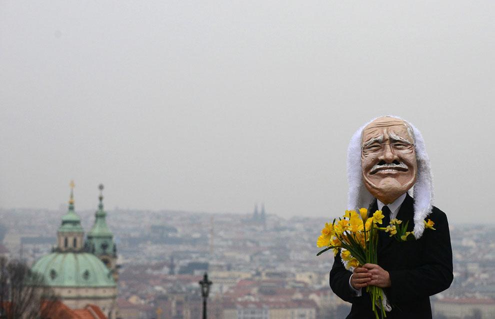 Человек в маске президента Чехии Вацлава Клауса на  Карловом мосту в Праге. Провожает с цветами президента в отставку в день окончания его полномочий