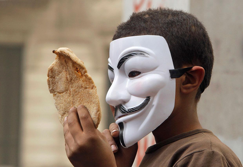 На демонстрации мальчик в маске Гая Фокса держит хлеб — символ нищеты