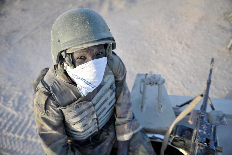 Солдат Уганды сидит наверху своего бронированного транспортного средства