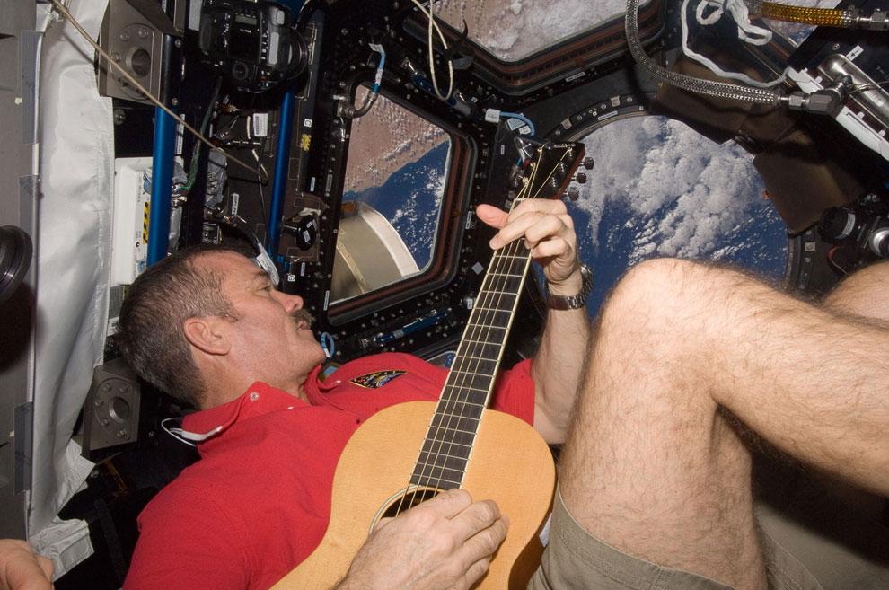 Астронавт Канадского космического агентства Крис Хэдфилд с гитарой на фоне видов Земли
