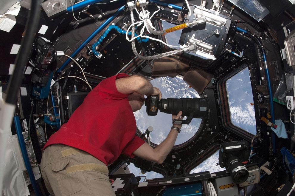 Канадец Крис Хэдфилд с телеобъективом, фотографирует Землю