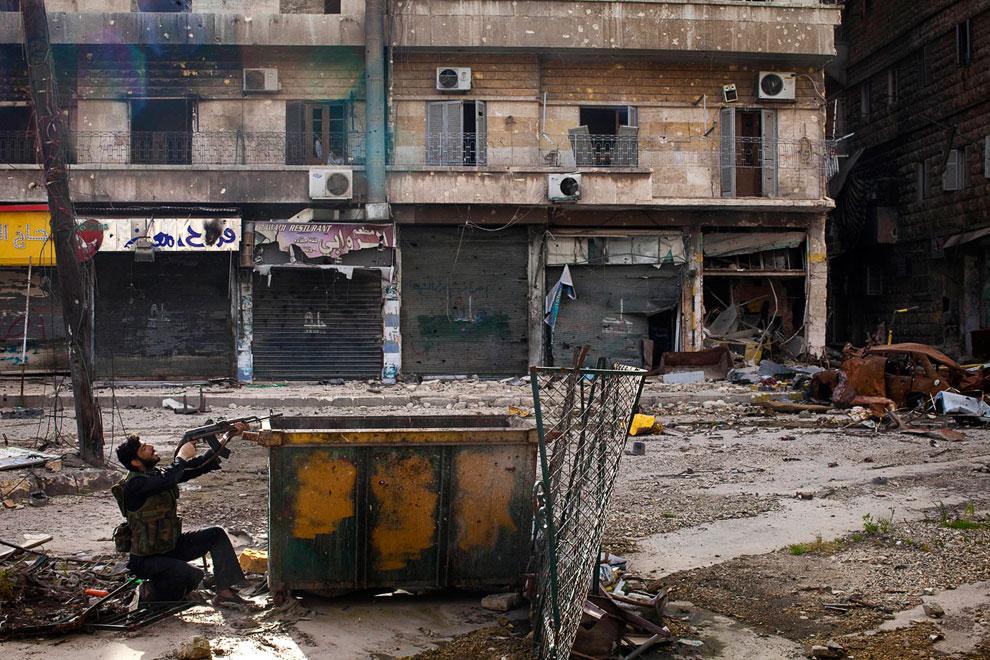 Сирийский мятежник постреливает из-за бака, Алеппо
