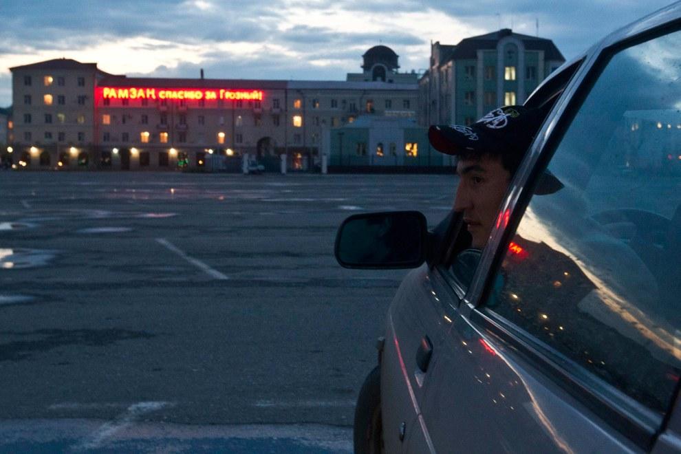Чеченский гопник молодой человек в машине перед зданием, на котором висит вывеска «Рамзан, спасибо за Грозный»