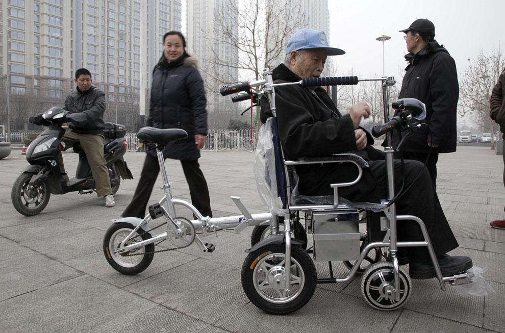 83-летний Чжан Юнцин демонстрирует свое изобретение в парке Пекина — инвалидную коляску-велосипед