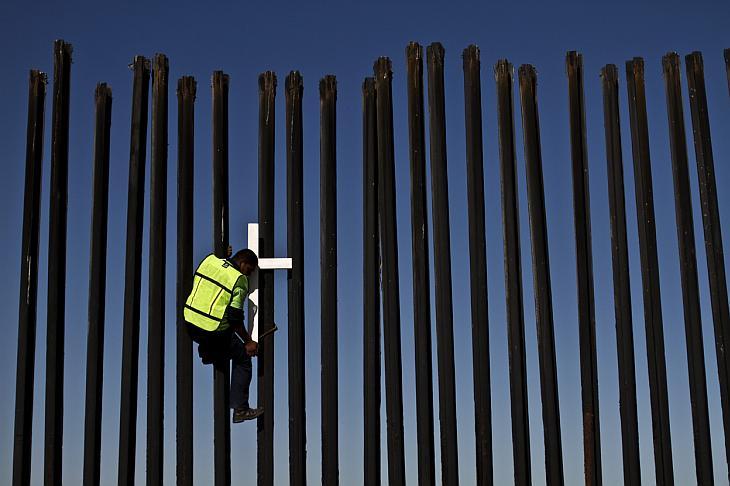 Депортированные мигранты перелезают через забор на американо-мексиканской границе в ходе подготовки к 6 ежегодному маршу мигрантов в Тихуане