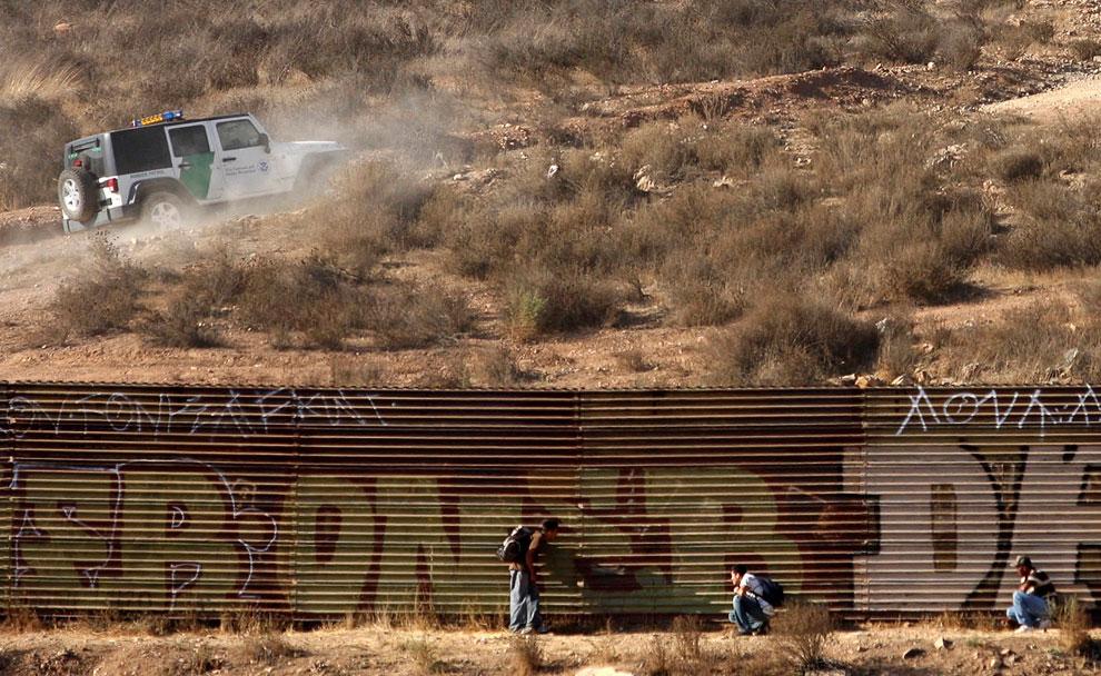 Одни из 500 000, попадающих в США нелегально, ждут у забора, пока проедут американские пограничники