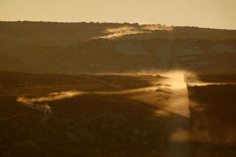 Пыль от мчащегося вдоль американо-мексиканской границы американского патруля в 90 км от Сан-Диего