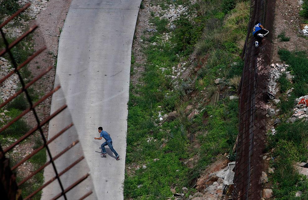 Нелегалы пересекают границу у города Ногалес, Аризона