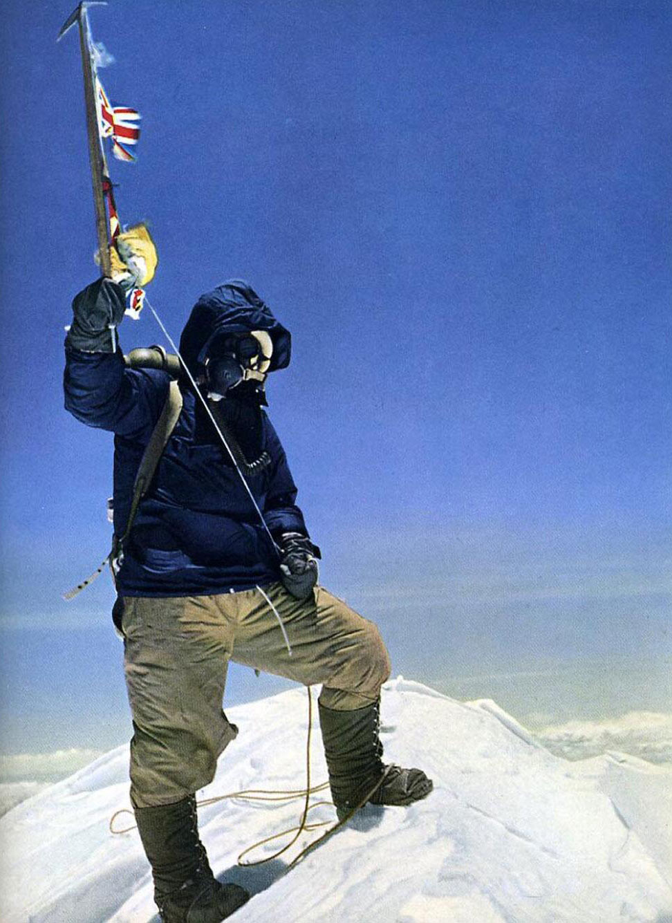 Почти двухметрового роста новозеландец Эдмунд Хиллари сфотографировал малорослого шерпа на снежном куполе с поднятым ледорубом, украшенным флажками ООН, Великобритании, Непала и Индии