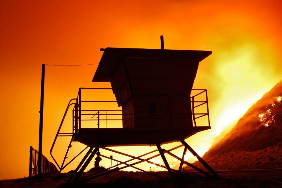 Огонь подбирается к спасательной башне на пляже в Калифорнии