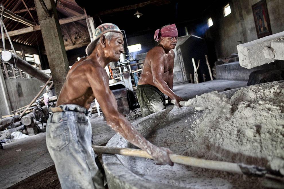Рабочие постоянно выравнивают лопатами сырье в «мукомольном аппарате», чтобы было равномерное давление