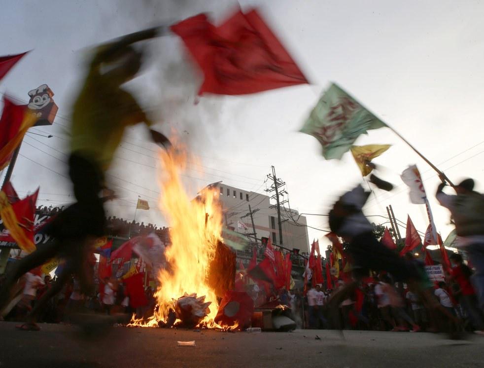 Рабочие в Маниле, Филиппины отметили Первомай 2013 сожжением чучел президента США Барака Обамы и президента Филиппин Бенигно Акино III перед президентским дворцом