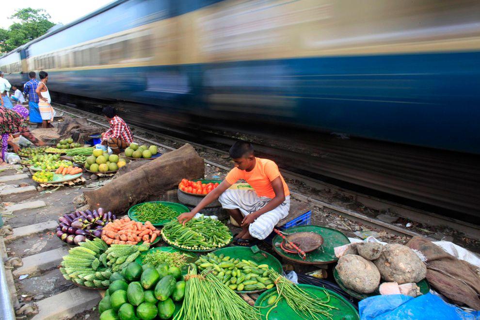 Продавцы овощей на фоне проходящего поезда в Дакке, Бангладеш