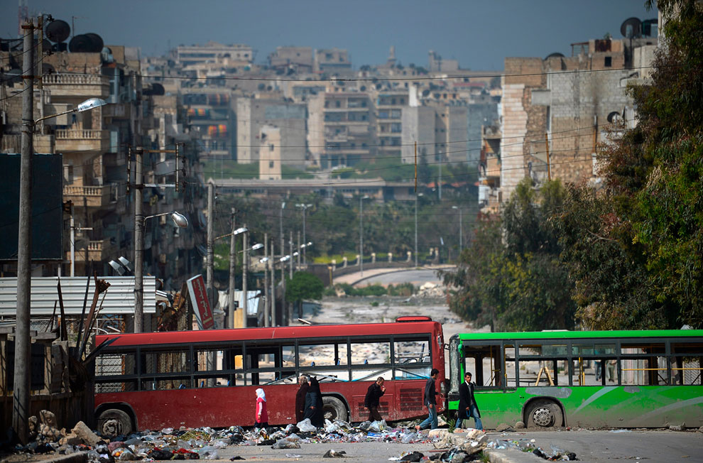 Баррикады посреди улицы и мирные жители Алеппо