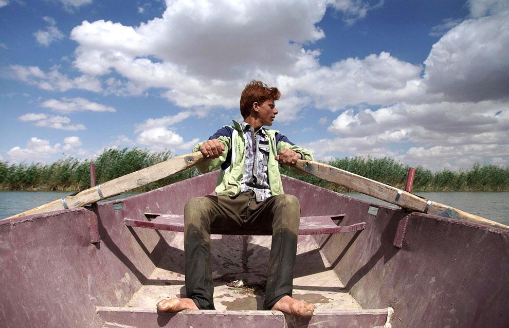 Мальчик подрабатывает тем, что перевозит на лодке людей с берега на берег