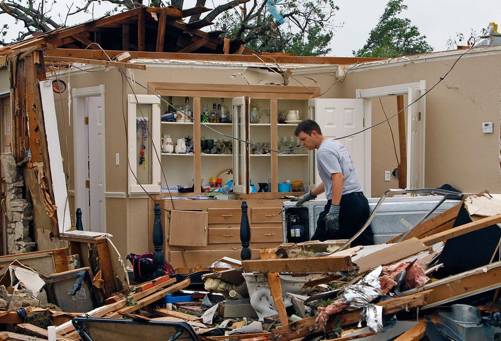 Хозяин бродит по остаткам своего дома, город Гранбери, штат Техас