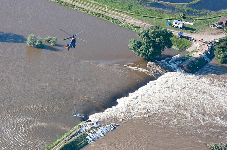Вертолет сбрасывает мешки с песком, чтобы исправить разрушенную дамбу на Эльбе в Германии
