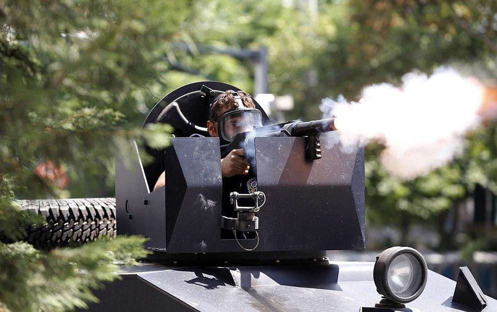 Полицейский стреляет по толпе протестующих слезоточивым газом