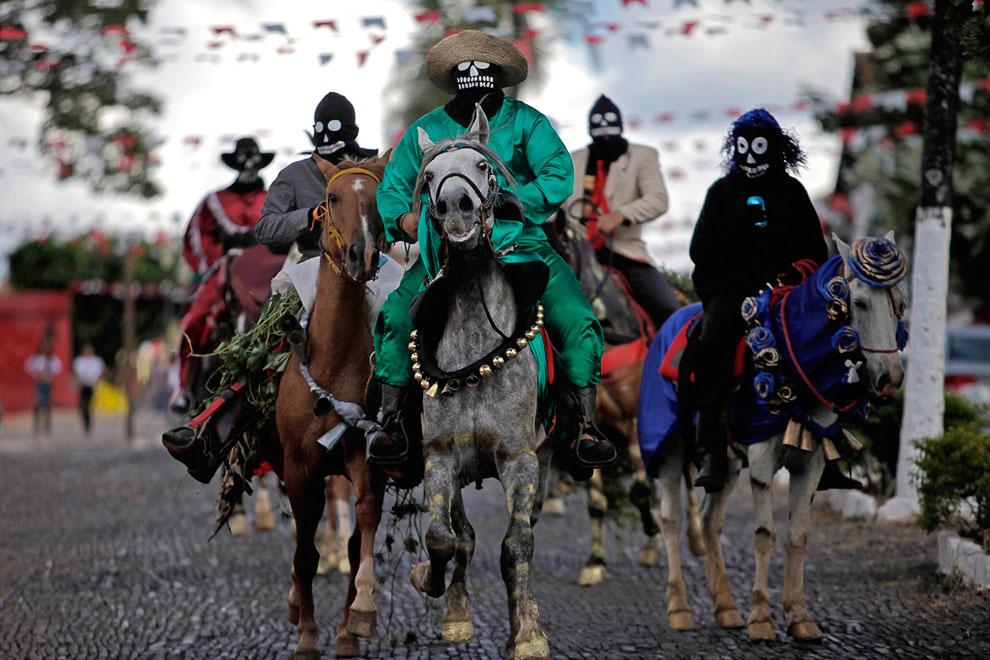 Люди в масках принимают участие в фестивале «Cavalhadas»,