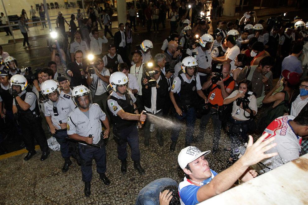 Полицейский распыляет слезоточивый газ на демонстрантов в городе Бразилиа