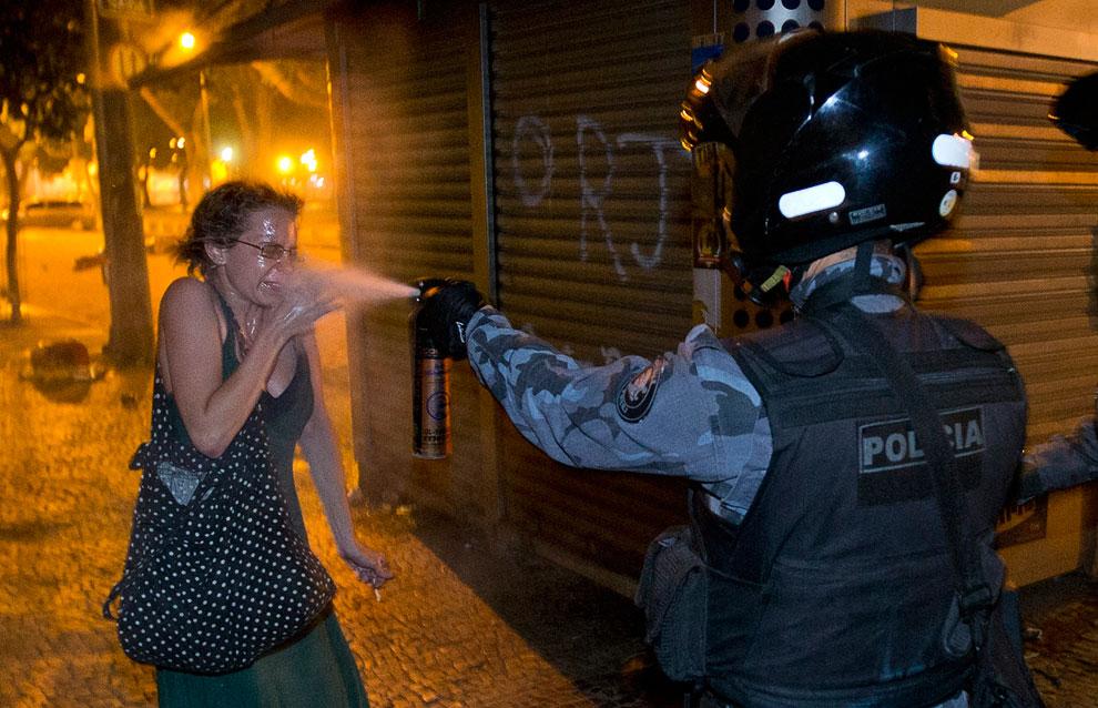 Полицейский зачем-то распыляет слезоточивый газ прямо в лицо одиночной демонстрантке, Рио-де-Жанейро, Бразилия