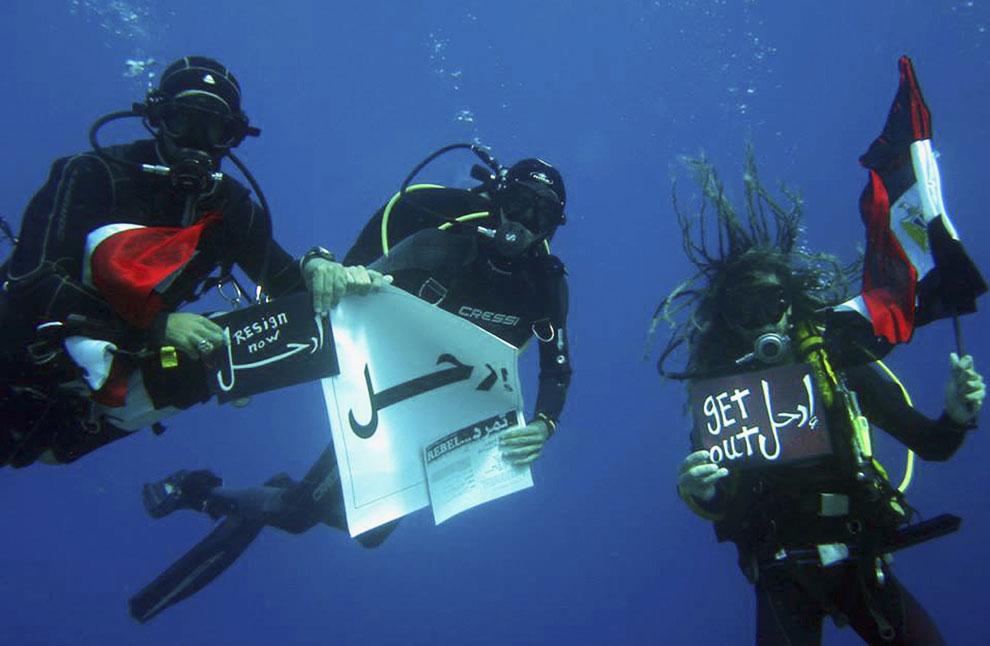 Некоторые протестуют даже под водой. На фотографии: аквалангисты держат плакат «Уходи». Шарм-эль-Шейх
