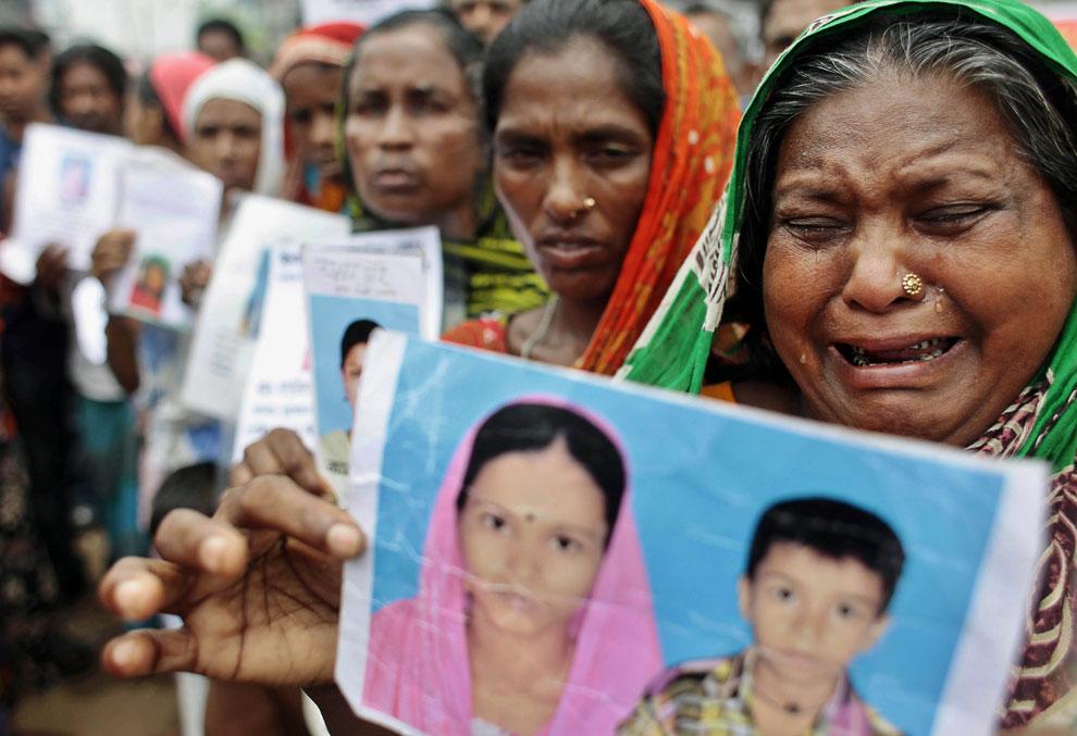 Женщины с фотографиями погибших и пропавших без вести родственников требуют компенсации от властей и владельцев рухнувшей фабрики, Бангладеш