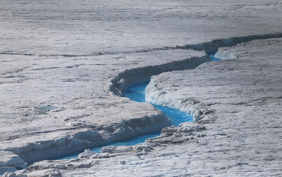 Таяние ледников. На фотографии видна талая вода, текущая вправо по огромной проталине