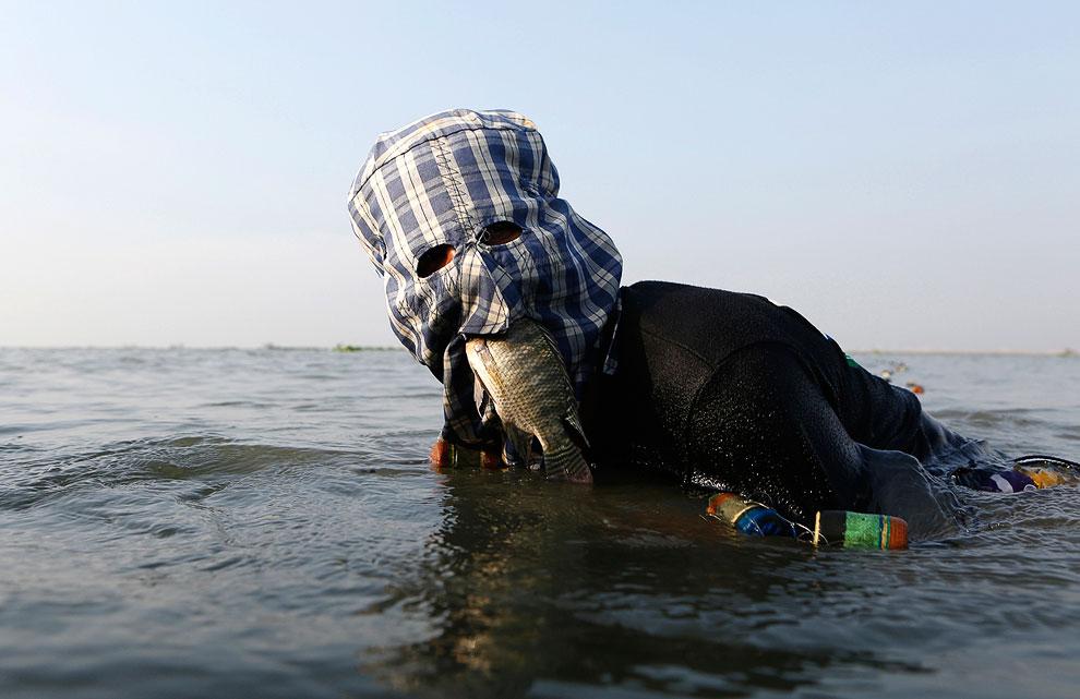 Рыбаки из Манилы во время рыбалки одевают маски, чтобы спасти лицо от палящего солнца