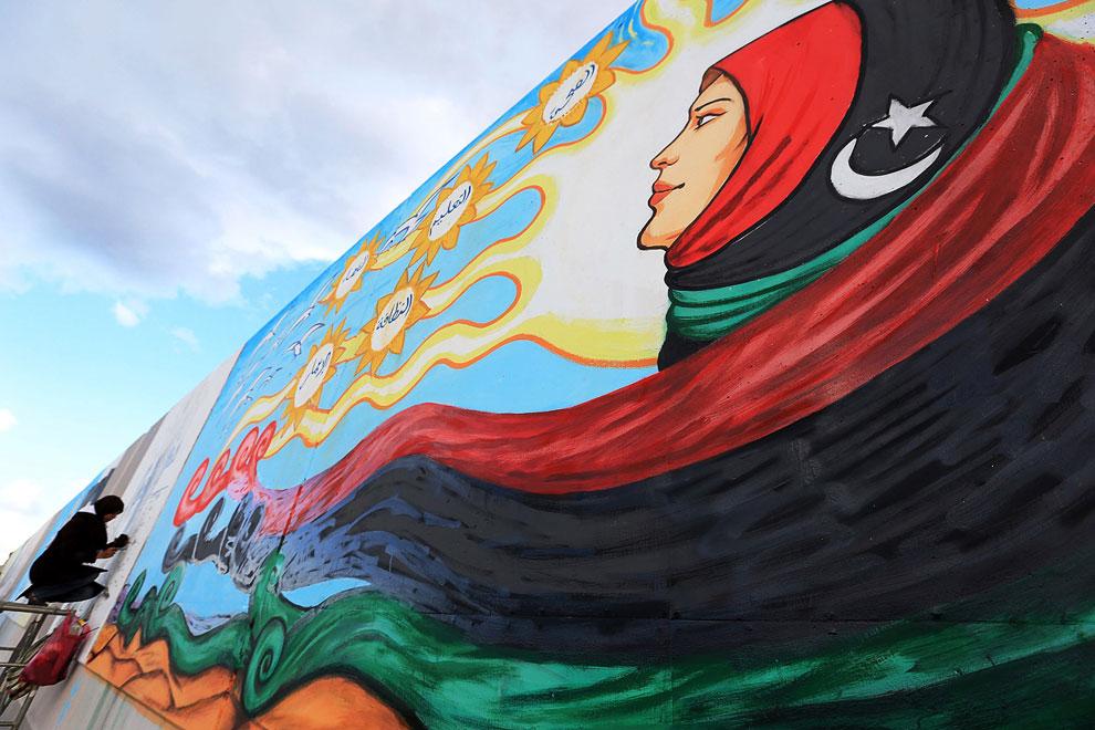 Художник на стене в Триполи создает большое панно. Раньше на этом месте было изображение Муаммара Каддафи