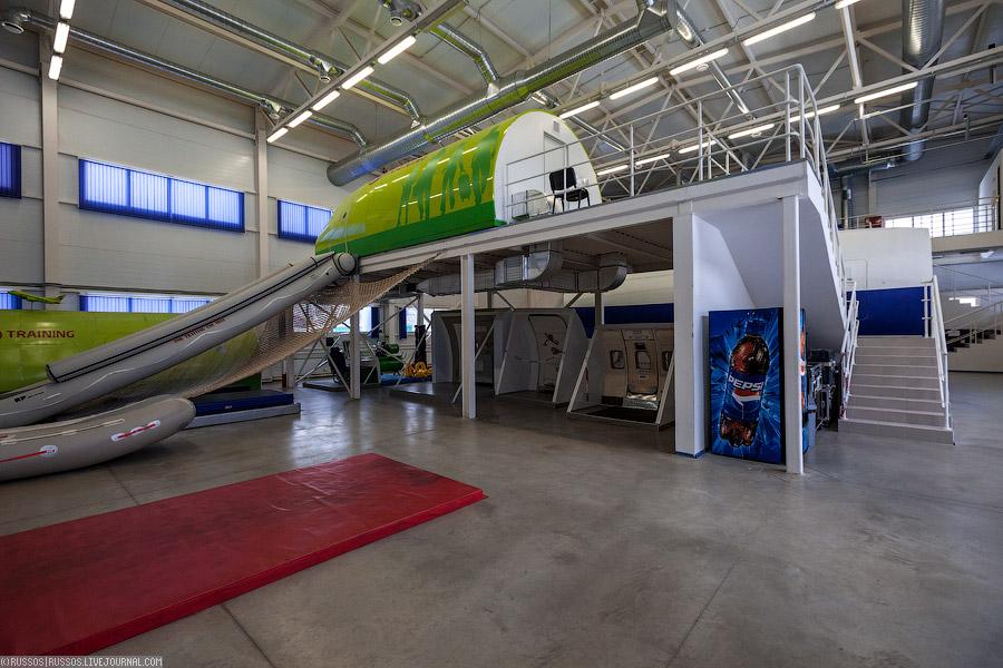 Учебный зал, где учат открывать двери, скатываться с трапа, спасать пассажиров и помогать им в случае аварийной посадки
