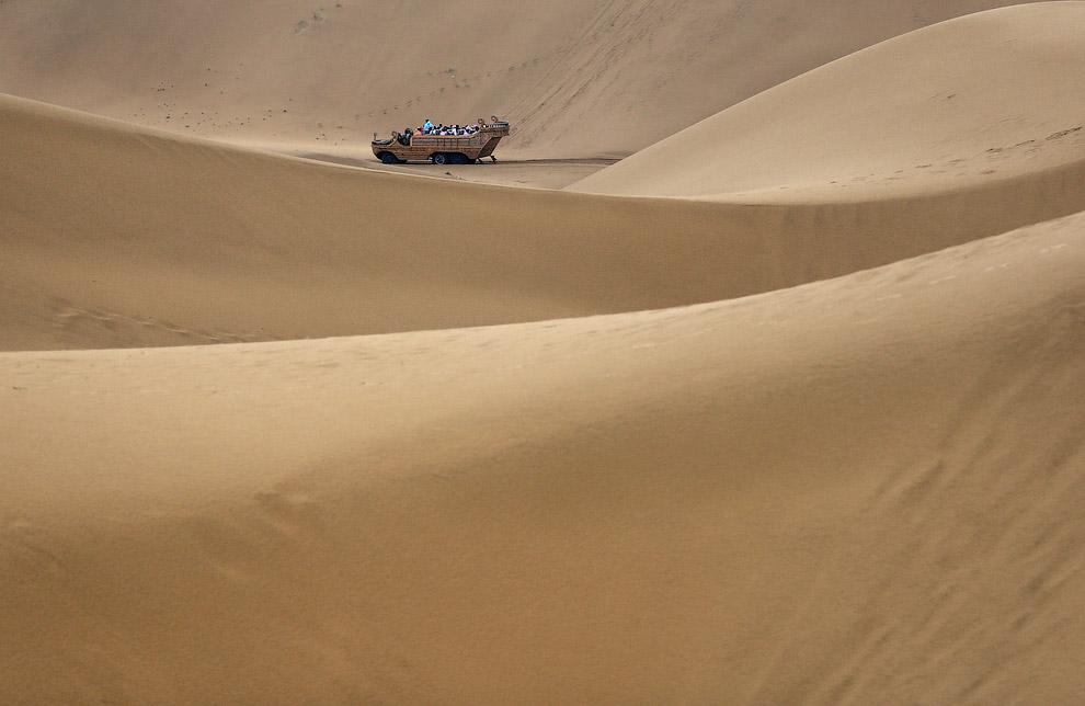 Туристы передвигаются по дюнам в необычных повозках