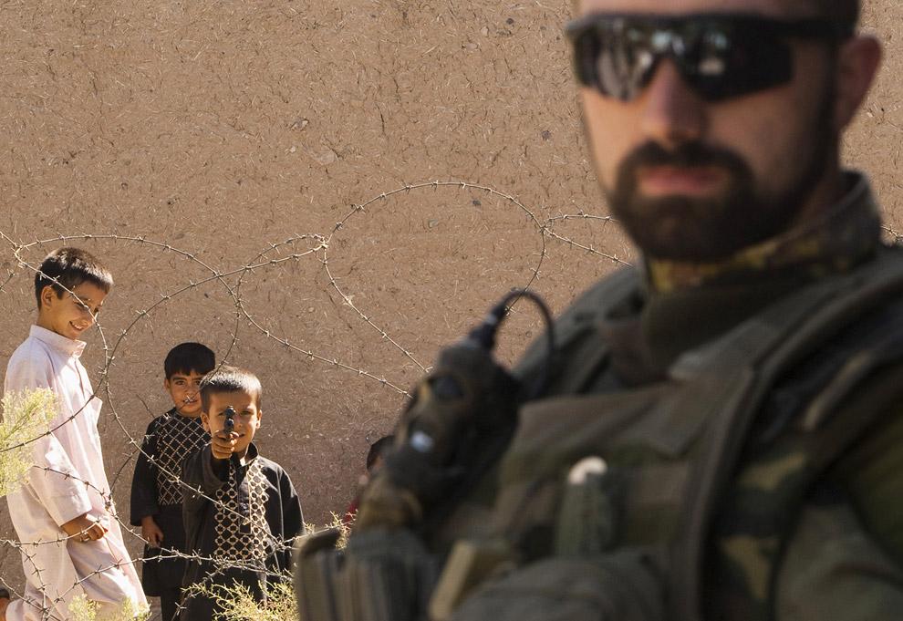 Итальянский солдат Международных сил содействия безопасности НАТО и мальчик с игрушечным пистолетом в тюрьме Герата